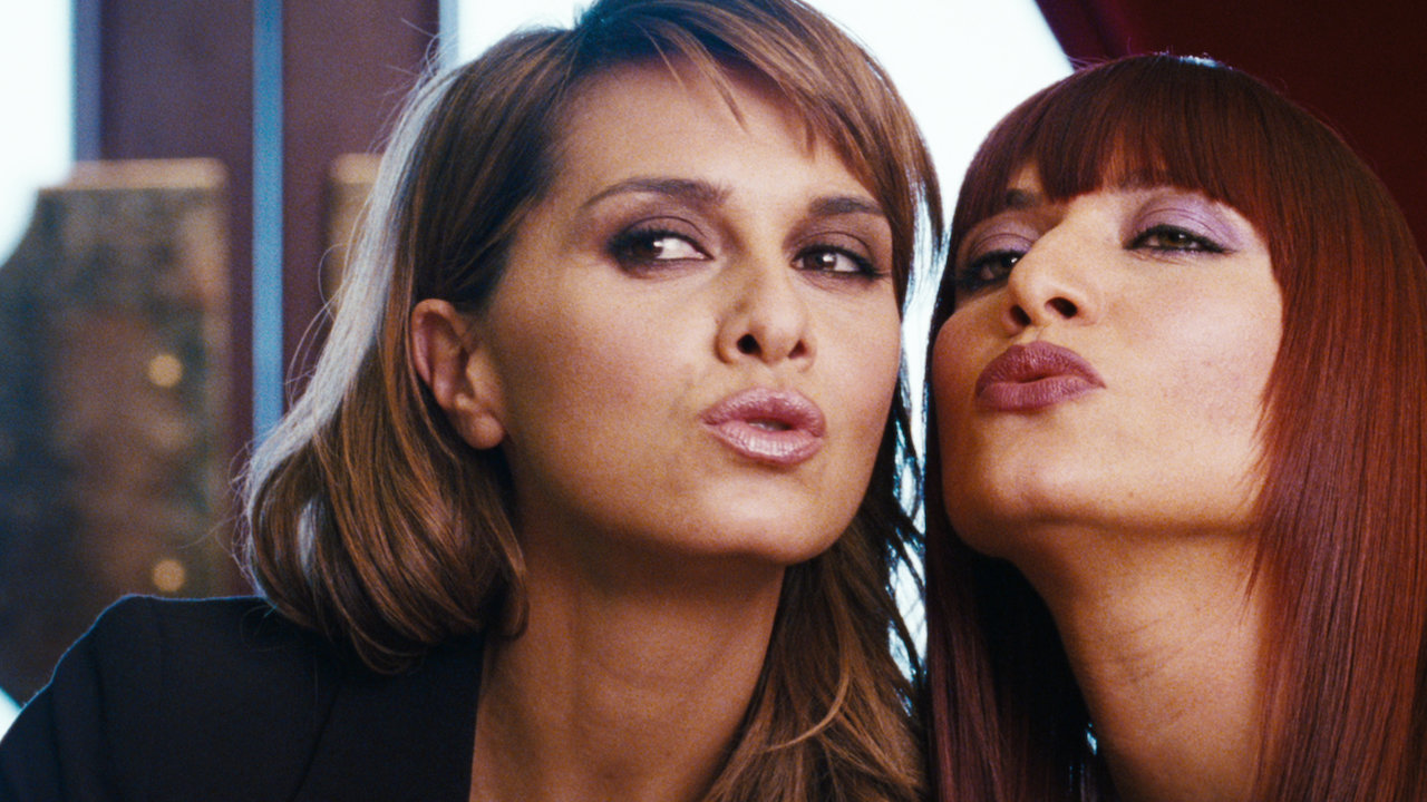 """Paola Cortellesi ed Anna Foglietta in una scena di Nessuno mi può Giudicare. Eva sta insegnando ad Alice i """"trucchi"""" del mestiere. Le due, truccate, stanno facendo facce strane ed hanno le labbra chiuse."""